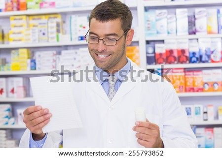 Happy pharmacist looking at prescription at the hospital pharmacy