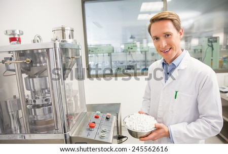 Happy pharmacist showing bowl of pills at the hospital pharmacy - stock photo