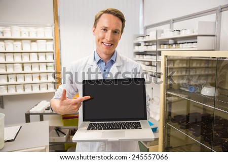 Happy pharmacist showing laptop screen at the hospital pharmacy - stock photo
