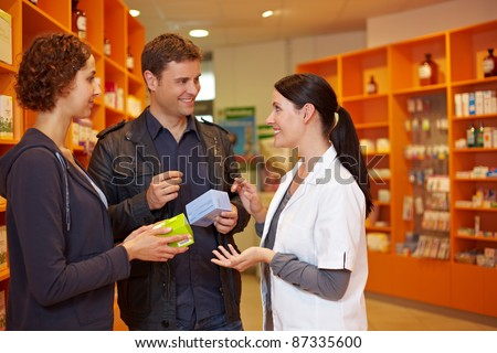 Happy pharmacist talking to a couple in a pharmacy - stock photo