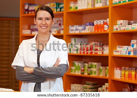 Happy pharmacist with her arms crossed in a drugstore - stock photo