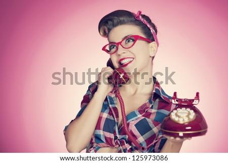 Happy pin up girl talking on retro telephone - stock photo