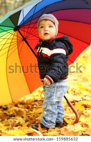 Happy playful child outdoors on autumn leaves. Little boy in the autumn park with rainbow umbrella. Background of autumn trees.Baby boy walking in the park - stock photo