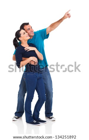 happy playful couple pointing away on white background