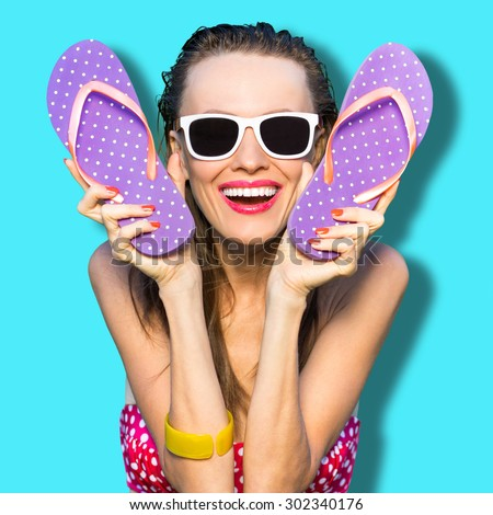 Happy playful girl with flip flops wearing sunglasses. Cheerful woman enjoy her vacation have fun - stock photo