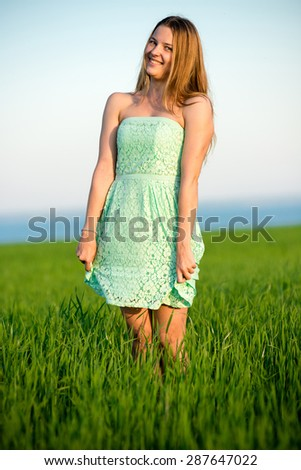 Happy playfull vitality freedom girl stands in green field. Woman lifestyle - stock photo