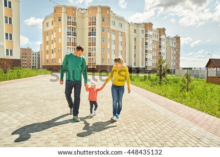 happy playing family outdoors. young parents with a baby for a walk in the summer. Mom, dad and child - stock photo
