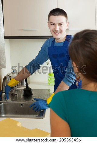 happy plumber in  repairing a running water  for  housewife