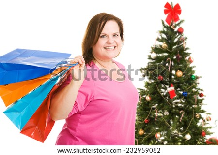 Happy plus sized model holding shopping bags, standing in front of a Christmas tree.  Isolated on white.   - stock photo
