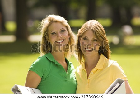 Happy portrait of young women holding folders outdoors