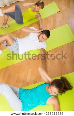 Happy positive adults at group training in fitness club. Focus on girl  - stock photo