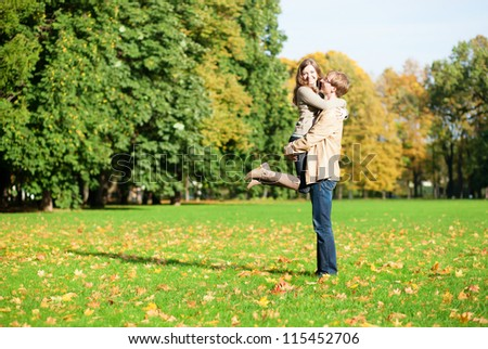 Happy positive couple hugging in park - stock photo