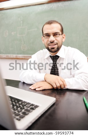 Happy positive teacher with laptop on desk in classroom