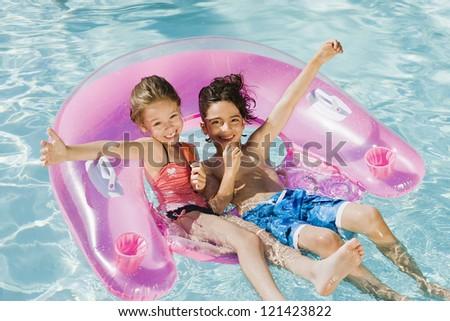Happy preadolescent friends enjoying in swimming pool - stock photo