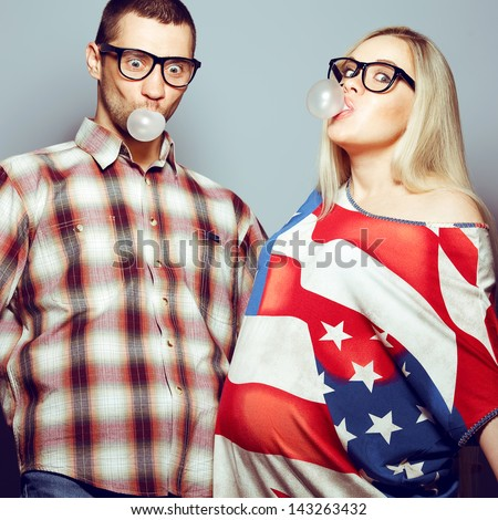Happy pregnancy concept: portrait of two funny hipsters (husband and wife) in trendy glasses and clothes playing with their bubble gums. Studio shot