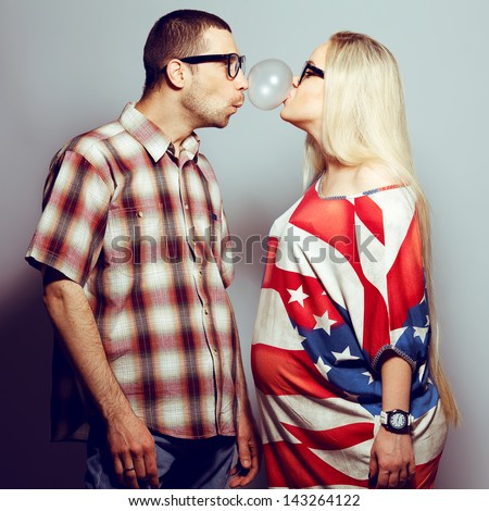 Happy pregnancy concept: portrait of two funny hipsters (husband and wife) in trendy glasses and clothes playing with their bubble gum. Studio shot