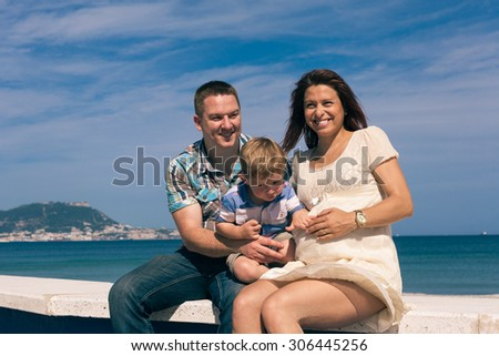 Happy pregnant couple and child boy enjoying sunny day on the coast in Spain.
