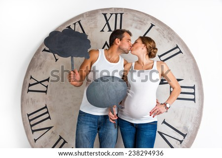 Happy Pregnant Couple dressed in white kissing and showing speech bubble banners looking happy excited and having idea on white background with giant clock - stock photo