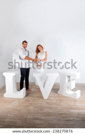 Happy Pregnant Couple dressed in white on white background with giant handmade letters of the word love - stock photo
