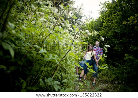 Happy pregnant couple is relaxing in nature