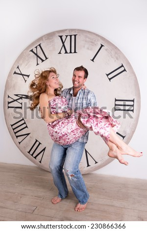 Happy Pregnant Couple on white background with giant clock - stock photo