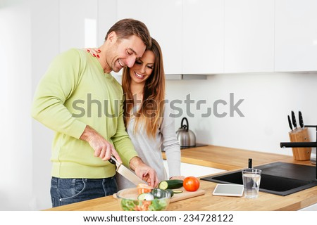 Happy pregnant couple preparing some food together - stock photo