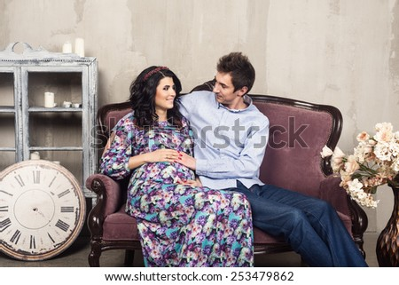 Happy pregnant couple sitting on the sofa at home - stock photo