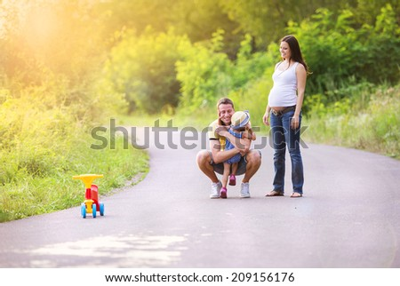 Happy pregnant family having fun during the walk in summer nature - stock photo