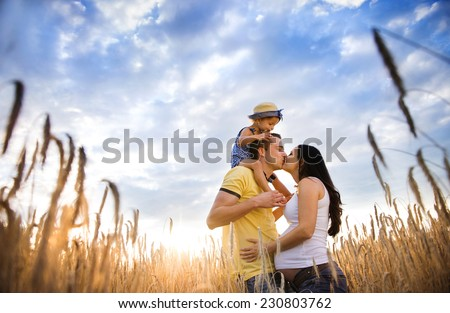 Happy pregnant family with little daughter spending time together in sunny field - stock photo