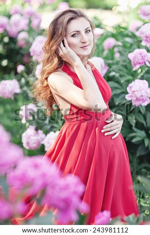 Happy pregnant woman hugging her stomach on the background of peony flowers,outdoor. Spring mood. - stock photo