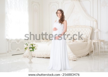 happy pregnant woman in a light interior - stock photo