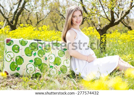 Happy pregnant woman in spring blossom garden is sitting on suitcase with apple pattern - stock photo