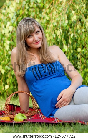 Happy pregnant woman in the park outdoors - stock photo