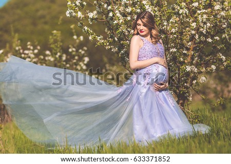 Happy pregnant woman is wearing fashion purple dress with big belly walking in spring garden with white flowers