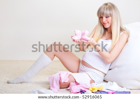 Happy pregnant woman looking at pink baby bootees - stock photo