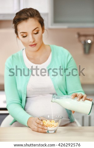 Happy pregnant woman making breakfast