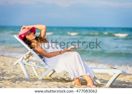 Happy pregnant woman resting lying on a lounger by the sea. Pregnant woman relaxing in the ocean while reading a book