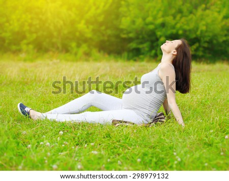 Happy pregnant woman sitting on the grass and enjoys sunny summer day