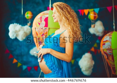 happy pregnant woman stands in the middle of beautiful studio