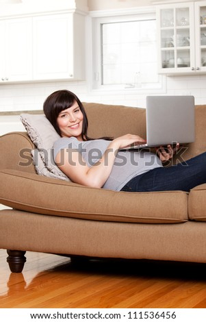 Happy pregnant woman using computer in living room