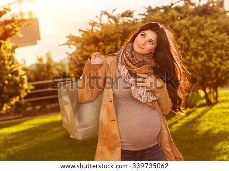 Happy pregnant woman with shopping bag in sunny autumn day on the backyard, preparing to baby birth, enjoying last days of pregnancy - stock photo