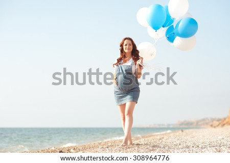 Happy pregnant woman 20-24 year old walking at beach with balloons. Summer traveling. Motherhood.
