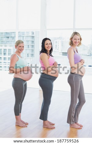 Happy pregnant women standing in a line smiling at camera in a fitness studio