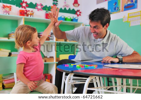 happy preschool teacher and child giving high-five - stock photo