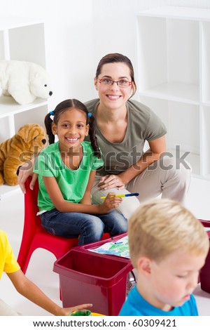 happy preschool teacher and students - stock photo