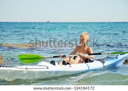 Happy preteen  boy on a kayak in sea - stock photo