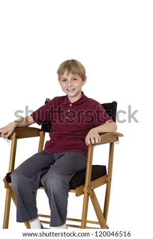 Happy preteen boy sitting on director's chair over white background