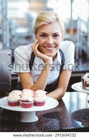 Happy pretty blonde showing her cake - stock photo