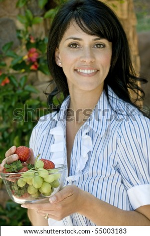 happy pretty brunette having a bowl of fruit outside on her home patio - stock photo