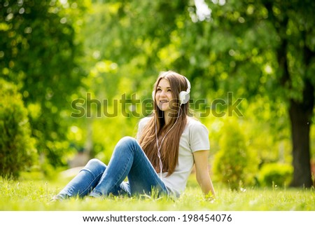 Happy pretty Caucasian teenage girl sitting on the grass while wearing blue jeans, white T-shirt and headphones, smiling and looking up, with blurred green foliage in the background - stock photo
